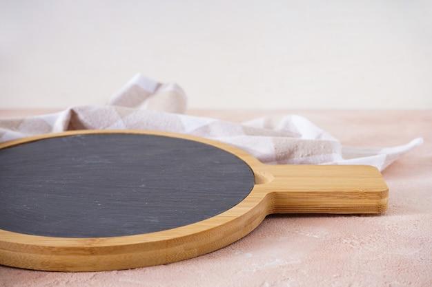 Tabla de cortar de madera con un paño de cocina sobre una mesa beige, primer plano.