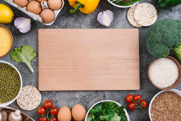 Tabla de cortar de madera rectangular rodeada de vegetales saludables.