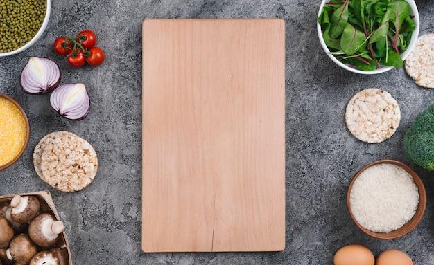 Tabla de cortar de madera rodeada de verduras y pasteles de arroz inflado sobre fondo de hormigón