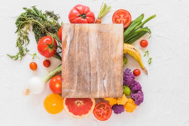 Tabla de cortar de madera sobre las verduras y frutas en el telón de fondo de textura blanca