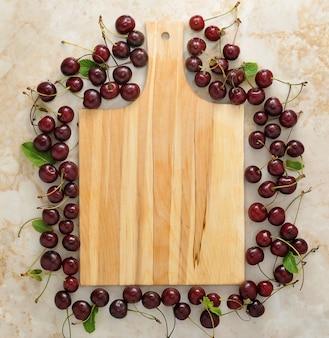 Tabla de cortar de madera vacía y esparcida alrededor de cerezas