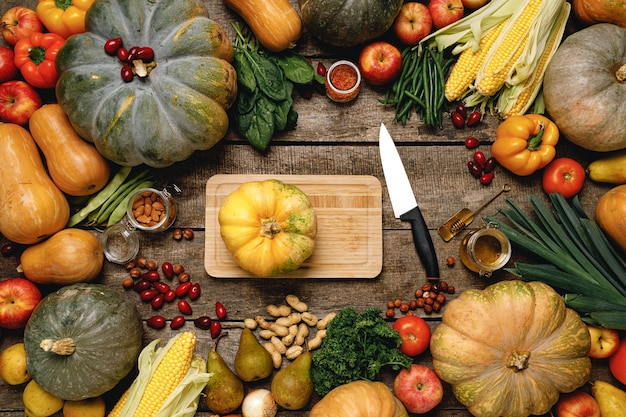Tabla de cortar de madera con verduras de otoño en la vista superior de la mesa de madera