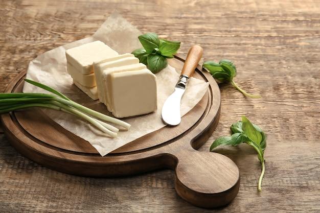 Tabla de cortar con mantequilla en rodajas sin envolver, cuchillo y verduras en la mesa de madera