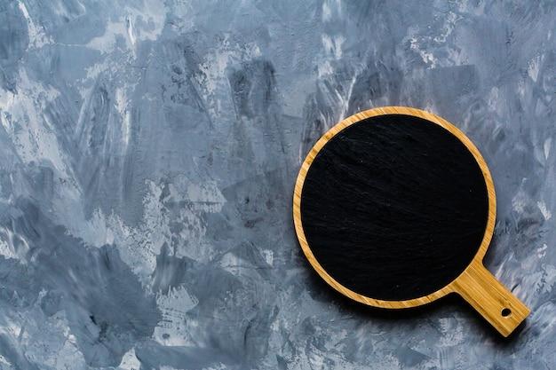 Tabla de cortar de maqueta sobre fondo de hormigón gris