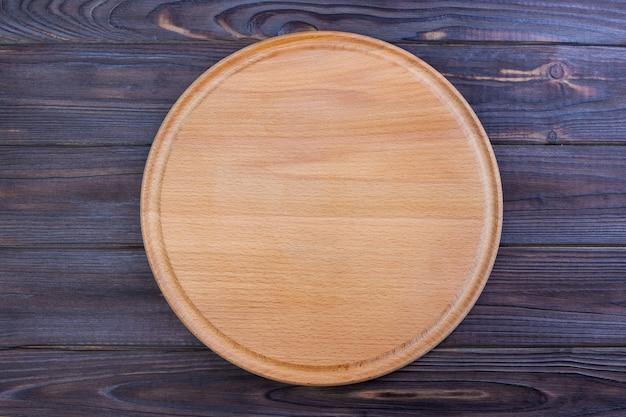 Tabla para cortar pizza en el fondo de la mesa