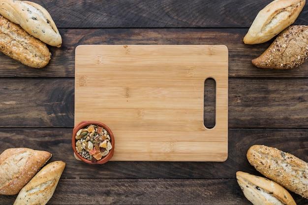 Tabla de cortar con plato de aperitivos y pan