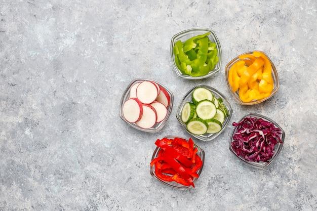 Tabla de cortar con rodajas de pimientos de colores sobre la superficie de la luz. rodajas de pimientos dulces en diferentes colores, ingrediente de ensalada de verduras, cocinar alimentos saludables, vista superior