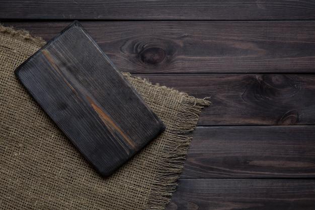 Tabla de cortar vacía en la mesa de madera oscura.