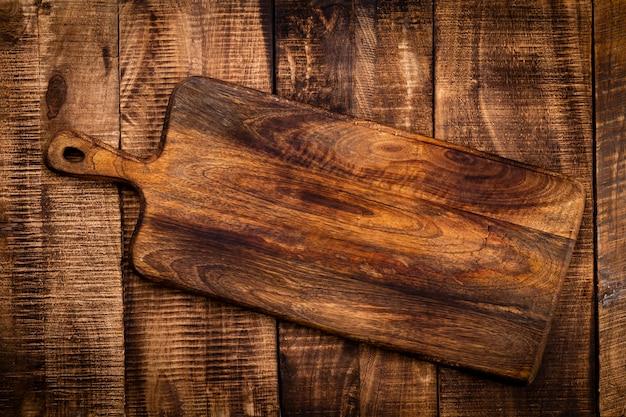 Tabla de cortar vacía tabla de cortar sobre una vieja mesa rustik
