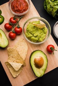 Tabla de cortar con verduras y salsas.