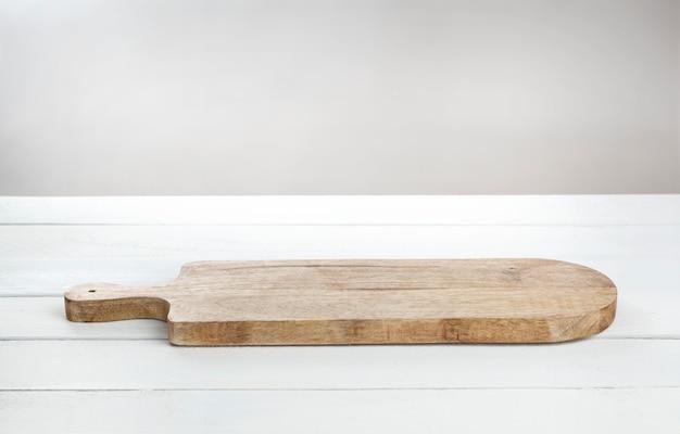 Tabla de corte para queso en mesa de madera blanca.