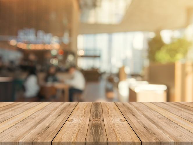 Tabla de madera la sobremesa vacía de fondo borroso.