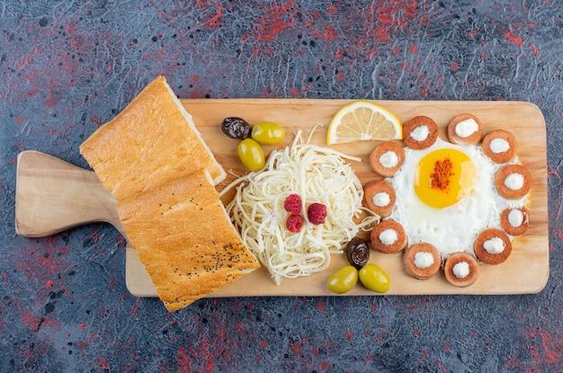 Tabla de desayuno con crepes, queso, limón y huevos.