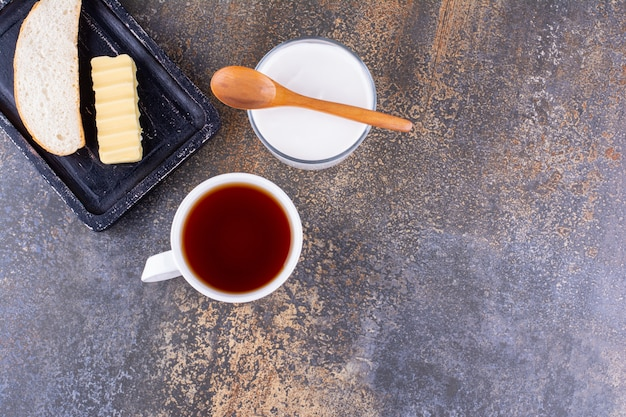 Tabla de desayuno con pan y una taza de té.