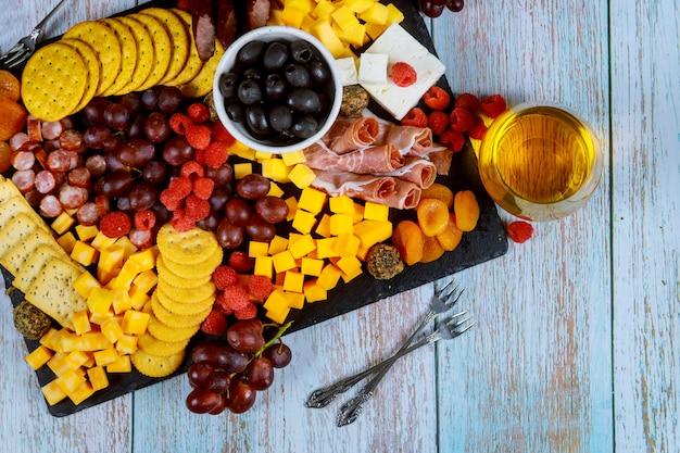 Tabla de embutidos con queso, aceitunas, frutas, jamón y vino en mesa de madera