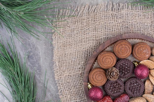 Una tabla de madera de almendras y galletas sobre fondo de mármol.