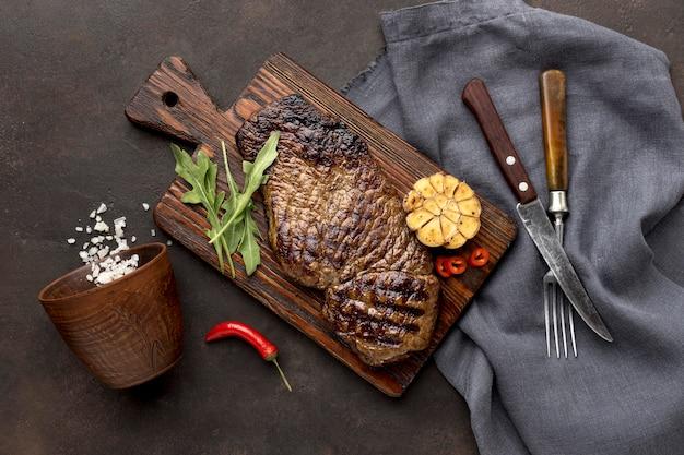 Tabla de madera con carne a la parrilla y cubiertos.