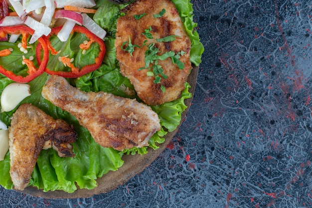 Una tabla de madera con carne de pollo al horno y verduras.