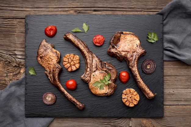 Tabla de madera con carne y verduras cocidas.