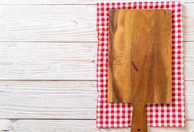 Tabla de madera de corte vacía con paño de cocina