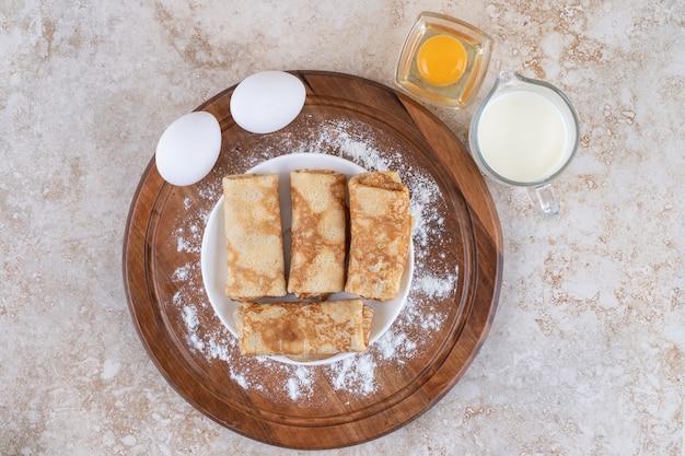 Una tabla de madera con deliciosas crepas y huevos crudos.