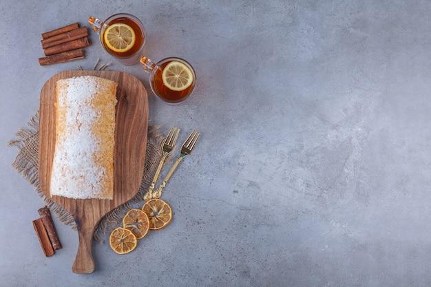 Tabla de madera de delicioso bizcocho con tazas de té sobre fondo de mármol.