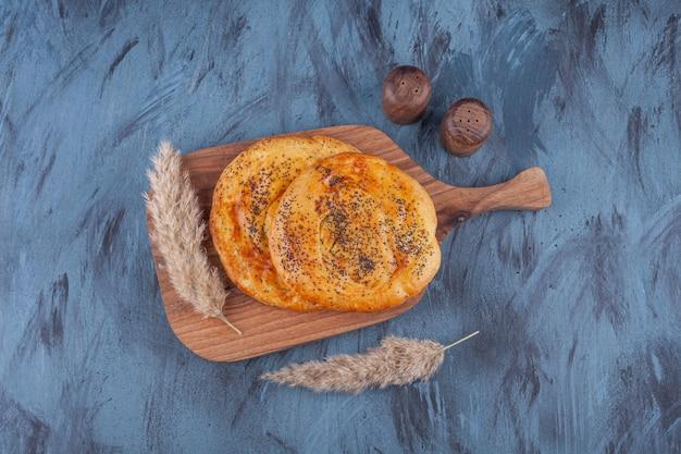 Tabla de madera de deliciosos pasteles fragantes sobre fondo de mármol.