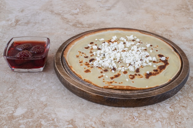 Una tabla de madera de finas crepas frescas caseras con mermelada de fresa