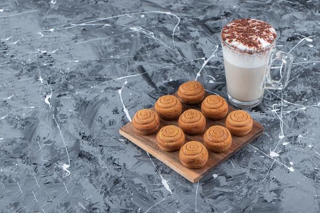 Una tabla de madera de galletas redondas dulces con una taza de cristal de sabroso café caliente sobre un fondo de mármol.
