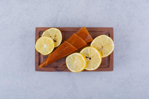 Tabla de madera de jugosos limones frescos y rollos de frutos secos y sobre mesa de piedra.