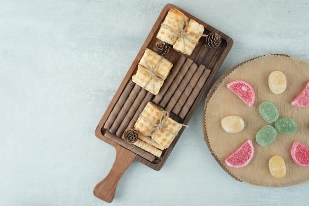 Una tabla de madera llena de pasteles y mermelada sobre fondo blanco. foto de alta calidad