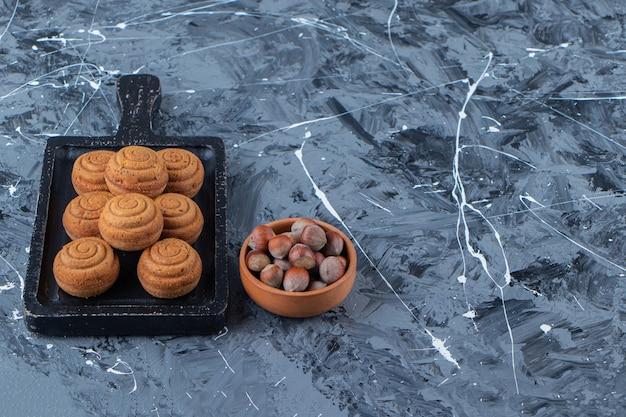 Una tabla de madera negra de dulces galletas redondas frescas para el té con nueces saludables sobre un fondo de mármol.