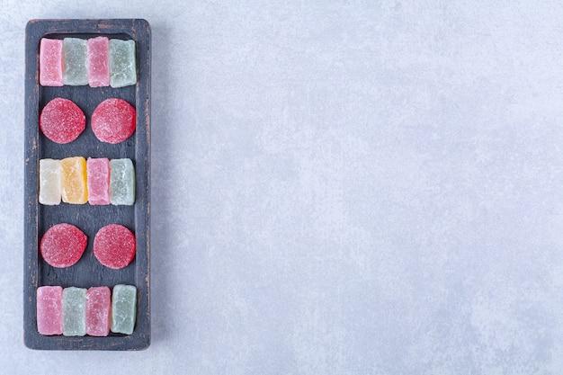 Una tabla de madera negra llena de dulces coloridos azucarados. foto de alta calidad