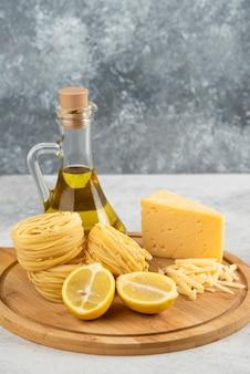 Tabla de madera de nidos de espaguetis, aceite, queso lemonnd en mesa blanca.