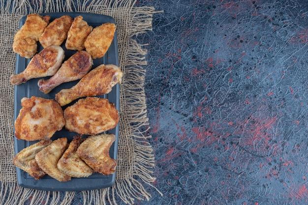Una tabla de madera oscura con carne de pollo al horno sobre una tela de saco.
