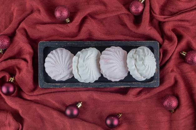 Una tabla de madera oscura con céfiros de vainilla y rosa con bolas de navidad.