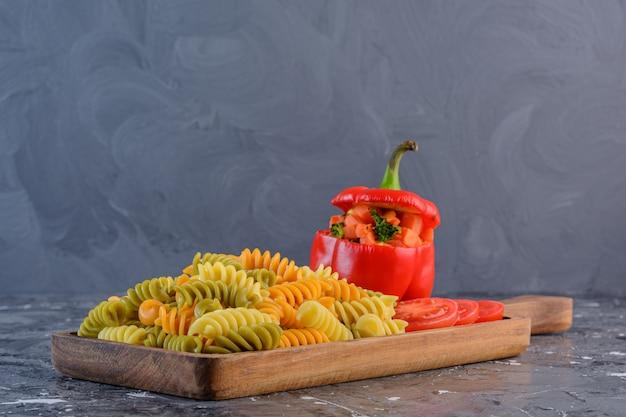 Una tabla de madera de pasta fusilli multicolor seca cruda con verduras.