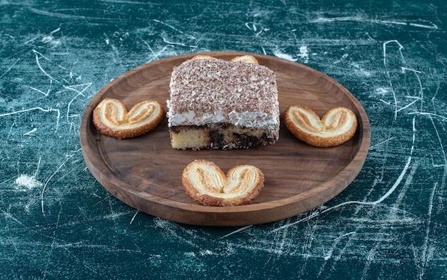 Una tabla de madera con pasteles dulces sobre un fondo azul. foto de alta calidad