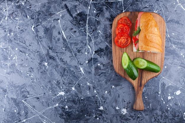 Tabla de madera de sándwich casero y verduras en rodajas sobre superficie de mármol.