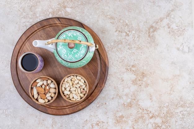 Una tabla de madera con tetera y nueces.