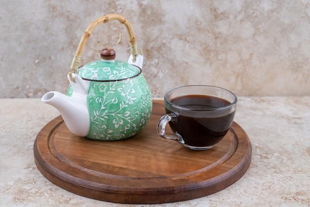 Una tabla de madera con tetera y una taza de té.
