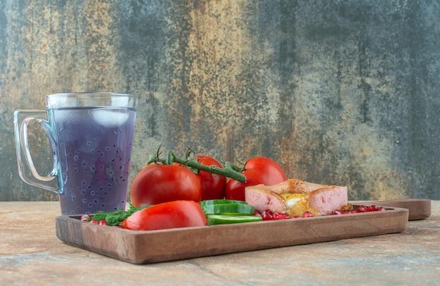 Una tabla de madera con tortilla y verduras con taza de bebida.