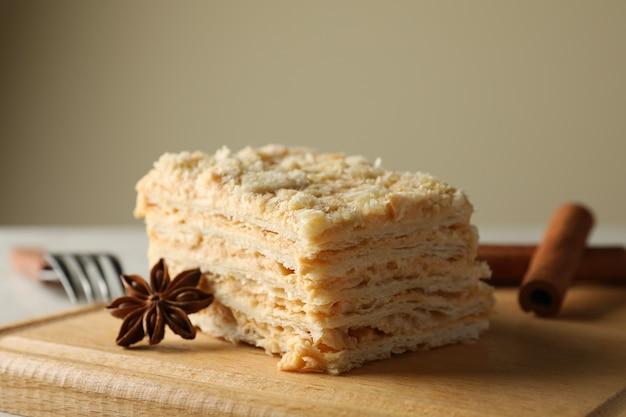 Tabla de madera con trozo de tarta de napoleón con canela