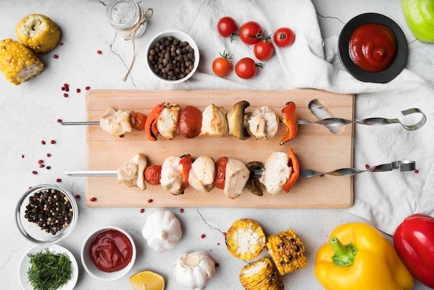 Tabla de madera de vista superior con brochetas de pollo y verduras a la parrilla