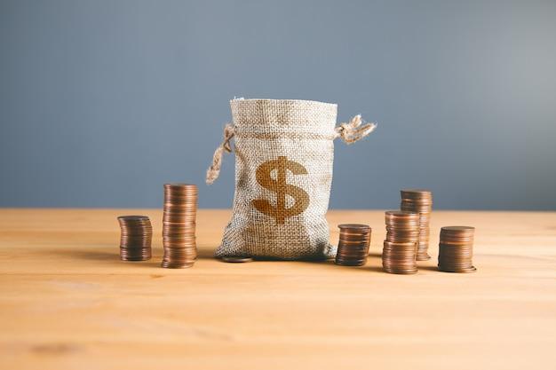 Tabla de monedas y bolsa de dólar en madera