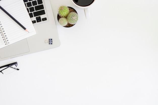 Tabla de la oficina de la vista superior con el ordenador portátil, la taza de café, el cactus, los vidrios, el papel de la libreta y el lápiz con el espacio de la copia en espacio de trabajo.