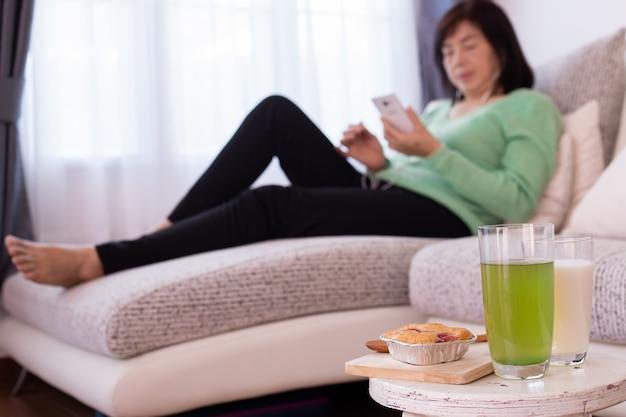 Tabla del postre con la muchacha hermosa en casa usando smartphone en el sofá, concepto de la atención sanitaria.