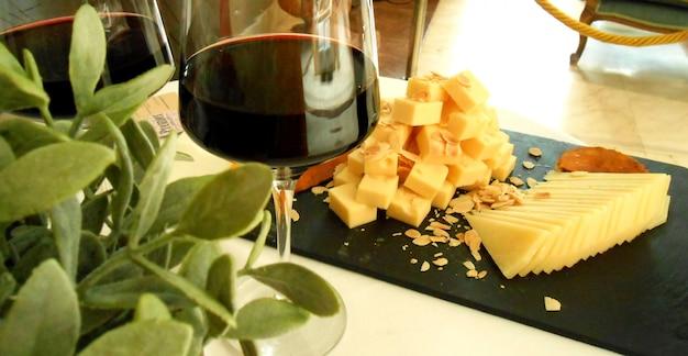 Tabla de quesos acompañada de copa de vino en la mesa varios
