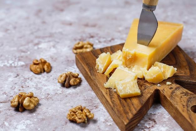 Tabla de quesos con queso duro, cuchillo de queso, copa de vino tinto, uva sobre superficie de hormigón marrón