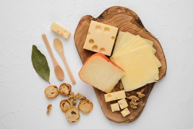 Tabla de quesos con rebanada de pan; hoja de laurel y nogal sobre superficie blanca